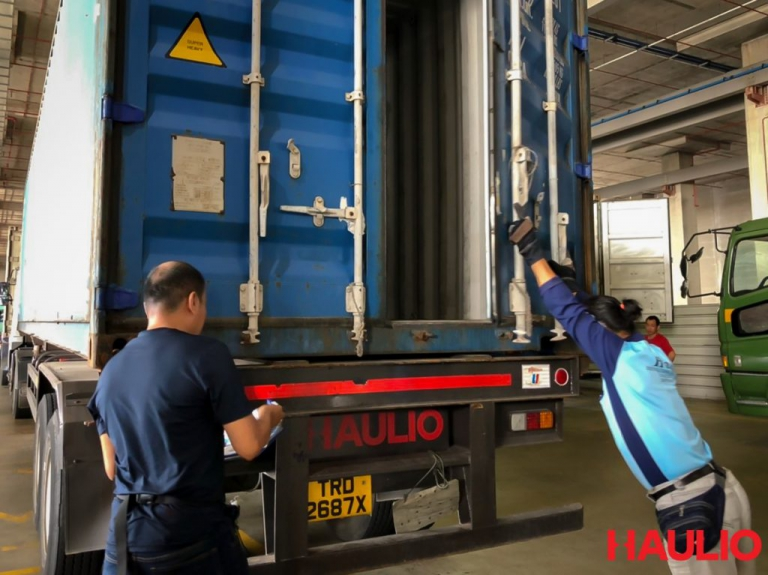 Uncle Foong closing the container door after inspection
