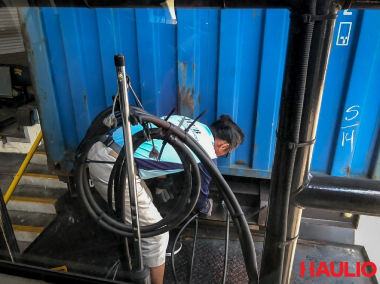 Uncle Foong ensuring that the container is securely latched onto the prime mover
