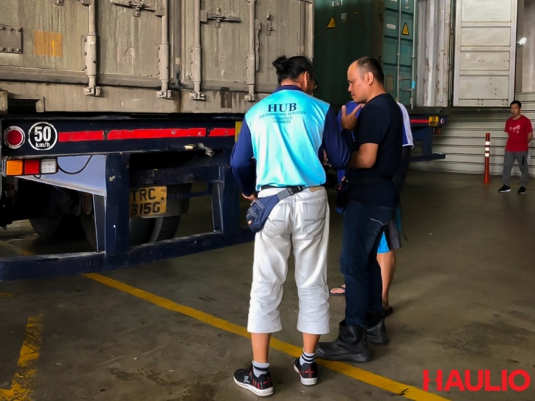 Uncle Foong talking to other truck drivers and the depot container inspector